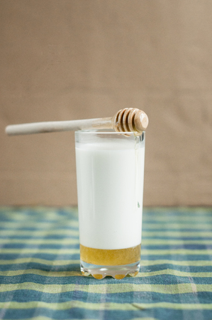 a glass of milk with honey  and wooden spoon on tablecloths Stock Photo