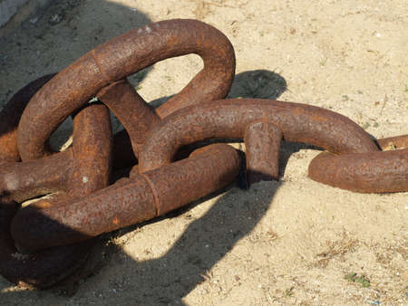 artefacts: Detail of an old rusted anchor chain on sand