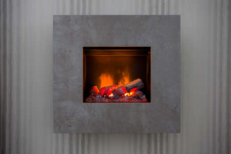 Detail shot of a modern simple fireplace with grey wall