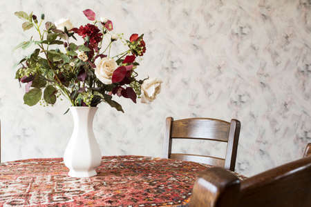 vintage living room with round dining table with flowers and pattern wallpaper old design Banque d'images