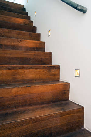 Wood stairs by night with led light in the white wall modern design