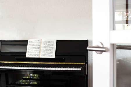 a black piano in a modern white living room with music sheets Reklamní fotografie