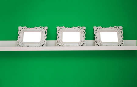 three white empty photo frames on a green wall and wooden shelf, isolated, space for text or photo
