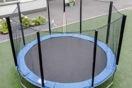 Blue trampoline with safety net on the lawn in garden