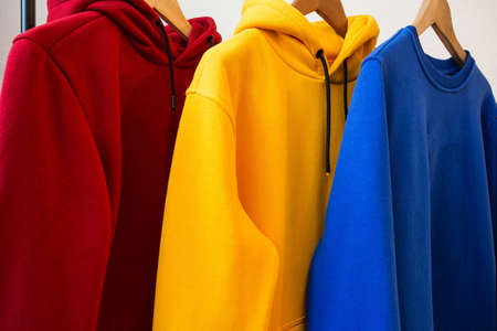 Colorful hoodies on hangers close-up modern design