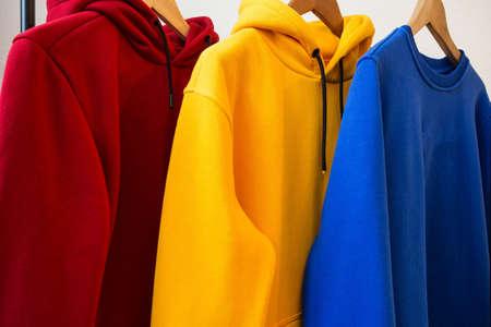 Coloridas sudaderas con capucha en diseño moderno de primer plano de perchas