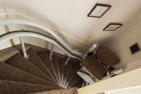 Mechanical chair lift taking disabled or aged people up and down stairs Senior, Stairlift for disabled