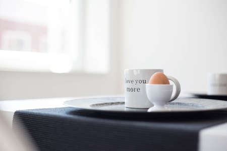 Delicious and healthy breakfast of a boiled eggs and a coffee mug on a white background, with the text i love you more close-up