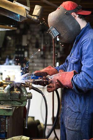 Welder is welding in the garage,industrial Worker labourer at the factory welding steel structure