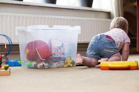 Baby playing alone with toys on a carpet on the floor at home