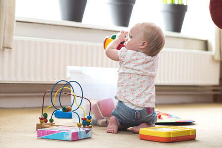Baby playing alone with toys on a carpet on the floor at home messy
