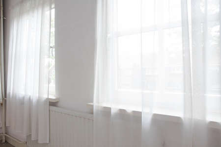 White net curtain against two windows in a house,