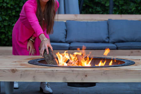 woman throws logs on fire pit in the garden on a summer day Reklamní fotografie - 124903094
