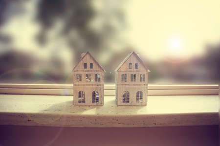 Modern window sill, closeup with two little white houses decoration