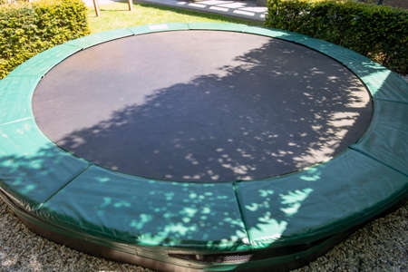 Green trampoline on the lawn in garden close-up empty