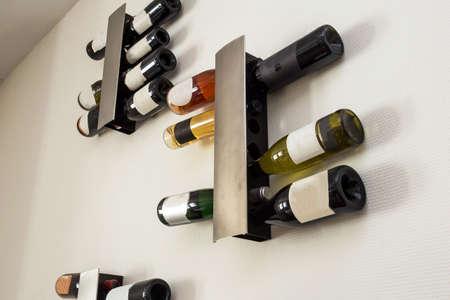wine bottles in modern rack on white wall in the living room Imagens