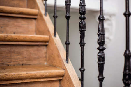Staircase Handrailing in Old Historic Building. Interior Decor of Vintage Stairs with Metal Ornament and White Wall Background. House Design Detail of Historical Stair Case with No People Close Up.