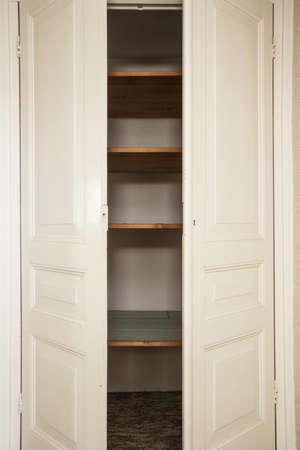 pared blanca recién pintada y puertas de armario, puertas abiertas, primer plano de almacenamiento Foto de archivo