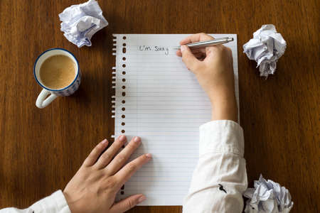 I am sorry written on paper with coffee on wooden table, hands of a person close-up