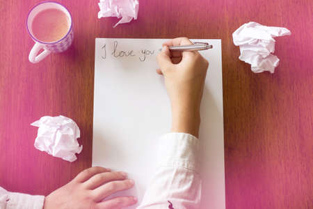 Woman writing a romantic letter with the text i love you , space for text beauty Reklamní fotografie