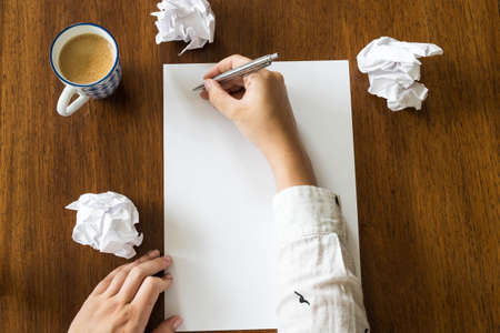 Blank sheet of paper and pen on bright wooden office desk with hands of a person close-up