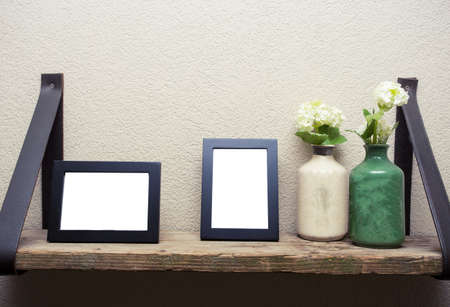 Two blank picture frames with decoration flowers on wood shelf industrial design