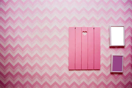 Blank wooden frames on pink striped wall, empty space for text, pink and purple retro design Reklamní fotografie