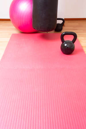 Kettlebell and pink yoga mat on the floor, sport concept space for text