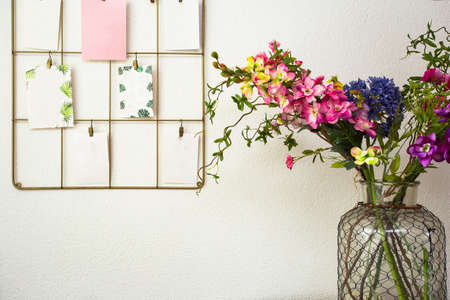 Bouquet of colorful flowers white wall and post cards hanging, modern interior