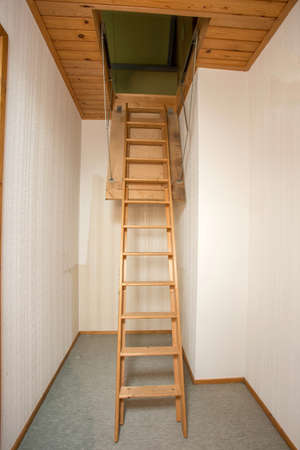 Wooden folding ladder to the attic, old empty house