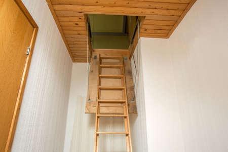 Scala pieghevole in legno per la soffitta, vecchia casa vuota
