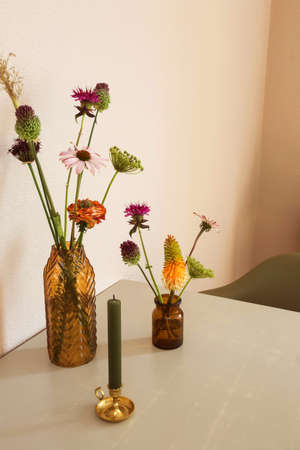 Two vases with flowers on the table retro modern design with white wall