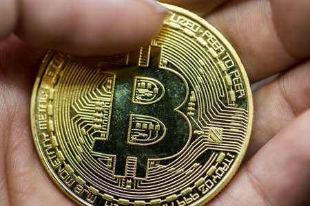 Golden Bitcoin in a man hand, Digitall symbol of a new virtual currency