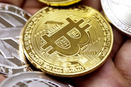 Golden Bitcoin in a man hand, Digitall symbol of a new virtual currency with black and white background Reklamní fotografie