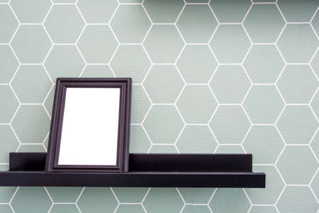 Blank picture frame on a shelf with blue and white color wallpaper background, retro design