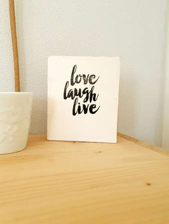Sign, Live Laugh Love on wooden shelf, modern decoration in retro home