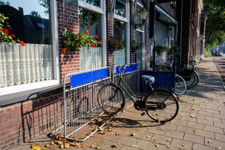 cozy street in the city with bicycle in bicycle stand near a pub