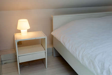Night light lamp next to bed in the bedroom, white wooden floor and bed, modern design