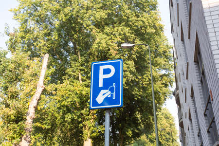 Paid parking area sign, Paid services on a background of green trees in the city