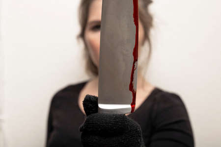 young woman holding bloody knife with black glove , crime scene killing