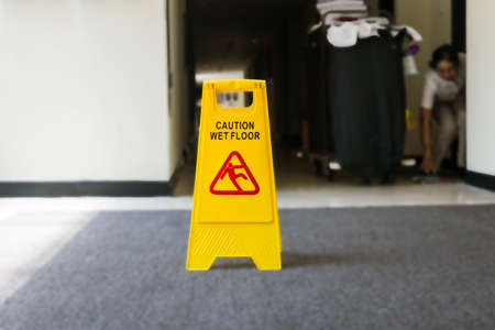 Sign showing warning of caution wet floor, cleaner on the background