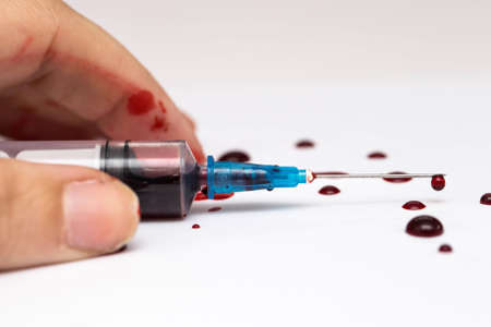 Hand lying on the floor with a Syringe splashing blood, scary theme suicide or overdose isolated Stok Fotoğraf - 131342905
