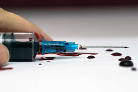 Hand lying on the floor with a Syringe splashing blood, scary theme suicide or overdose isolated