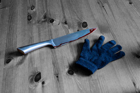 A black and white photo of a knife murder weapon and a glove on a wooden background. This image can also be used to represent crime scene evidence. horror theme