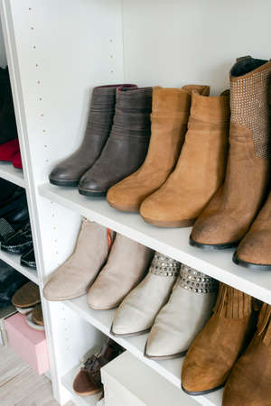 Collection of shoes sorted in shoe rack, brown colors, orginazed interior in a closed Stock Photo