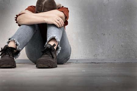 Młoda kobieta płacze i siedzi przy pustej ścianie, samotna smutna i przygnębiona dziewczyna trzyma głowę w dół