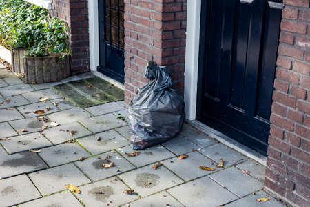 Garbage bag near a front door in a neighbourhood, ready for pick up