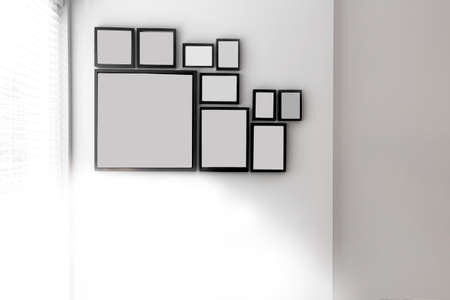 Group of various blank black picture frames on grey wall near a window with light, space for text