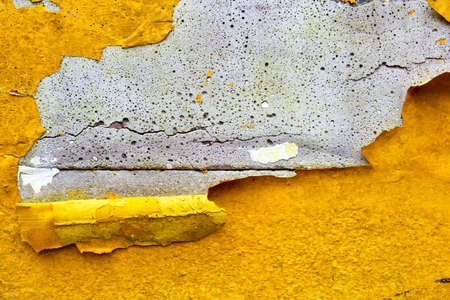 Concrete wall with yellow, orange peeling paint old cracked damaged rough bright background texture Zdjęcie Seryjne
