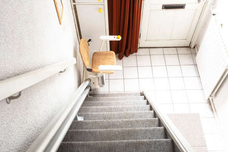 Automatic stair lift on staircase taking elderly people and disabled persons up and down in a house 免版税图像